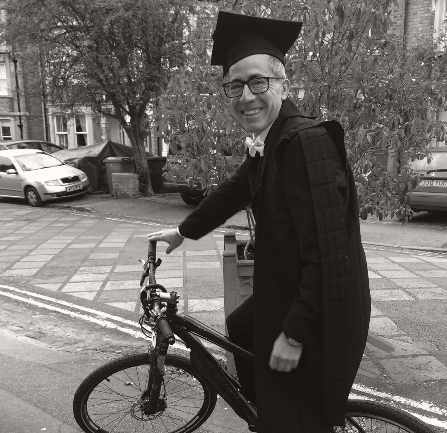 Marcelo Bravo in his academic dress and mortarboard, on-top of a bicycle.