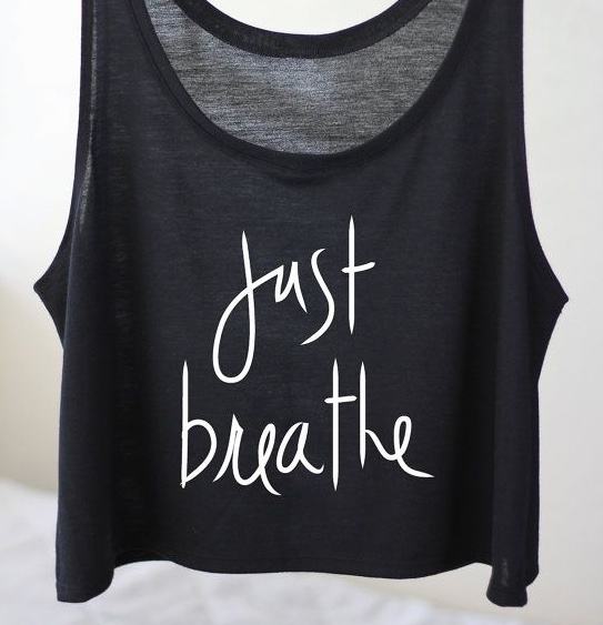 """A black vest with the words """"Just breath"""" in white curly text on the front"""
