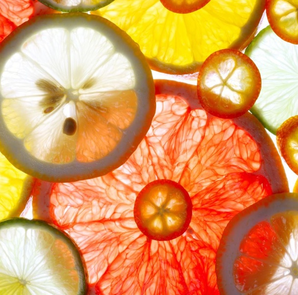 Various slices of fruit such as lemon, grapefruit, and orange placed on top of a white backboard.