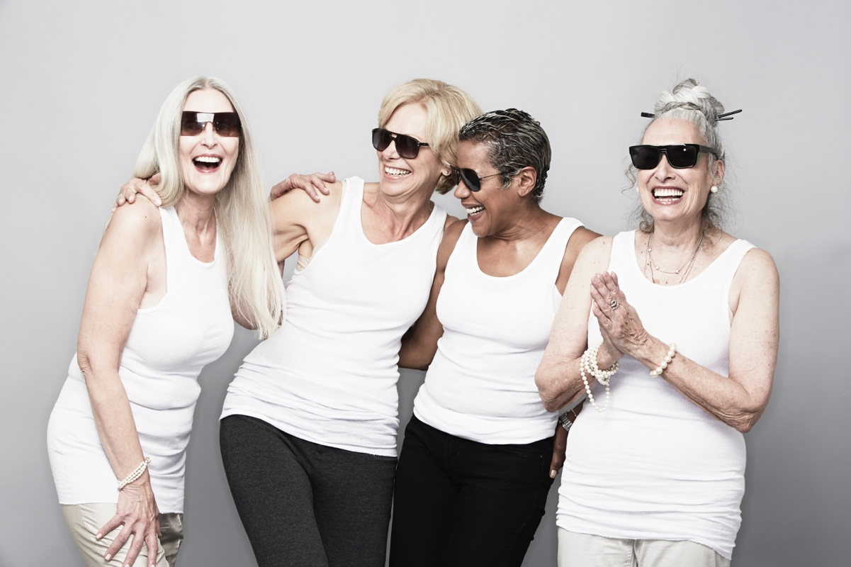 Four ladies wearing white and smiling, looking full of energy.